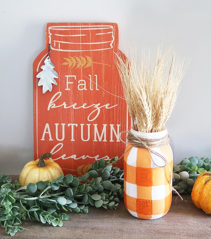 bricolage automne avec pot en verre repint de rouge et blanc avec des épis de blés et, plaque bois décorative en forme de bocal, potirons decoratives