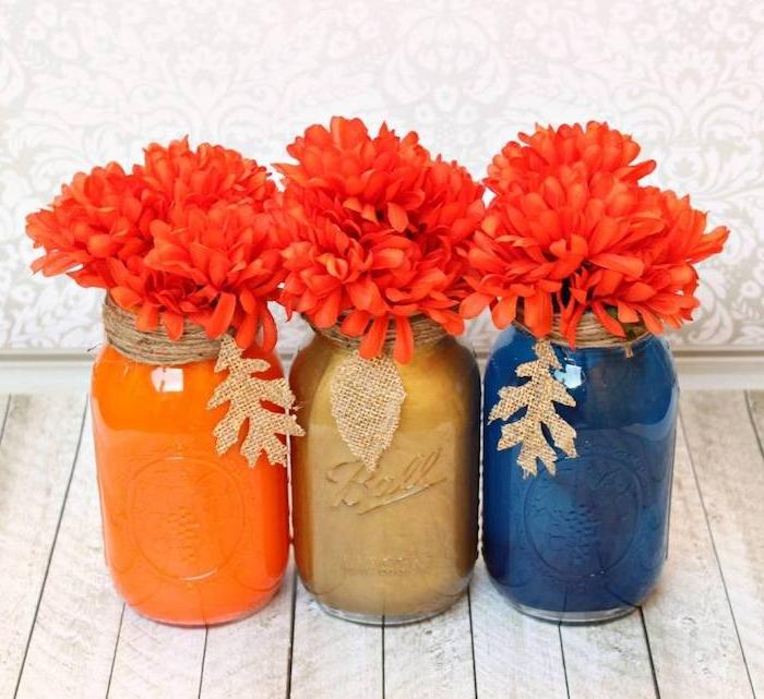 pots en verre repeints de peinture à l intérieur avec des fleurs orange, bord décoré de ficelle et feuilles de jute