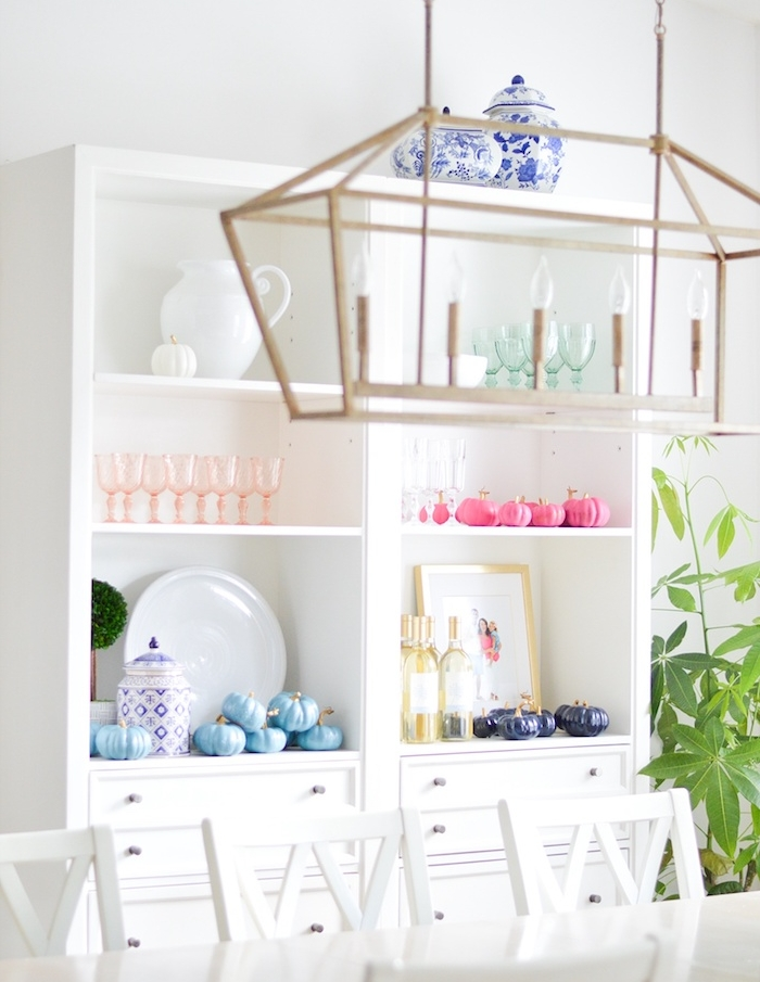 decoration avec potirons citrouilles repeintes de couleur violette, bleue et rose sur vaisselier blanc, table et chaise blanche