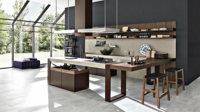 design intérieur contemporain dans une cuisine moderne à haut plafond avec plancher effet béton et mur foncé noir mat
