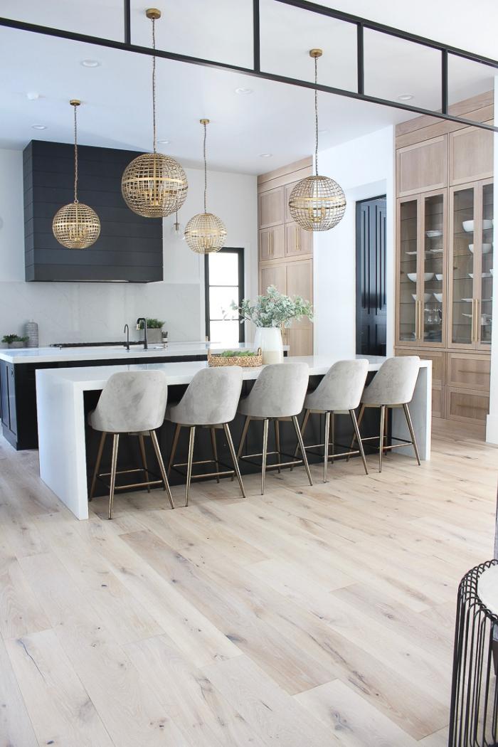 design intérieur contemporain aux murs blancs avec plancher bois, modèle chaises bar effet ciment, idée cuisine noir et blanc