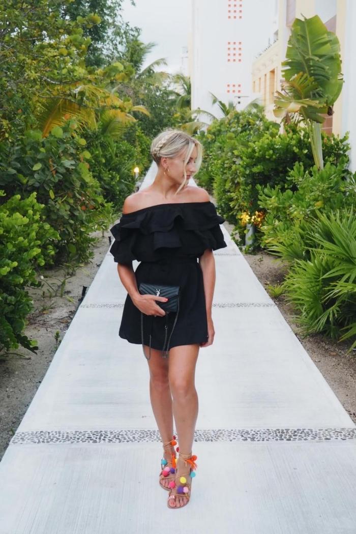 modèle robe noire courte avec décolleté à volants et pochette noire, modèle de sandales hautes avec pompons