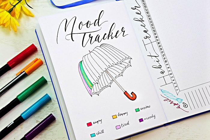 bullet journal tracker sous forme de parapluie avec code couleur, une page avec suivi d'humeurs et titre en calligraphie