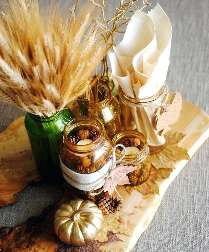 deco table automne, centre de table planche de bois avec pots en verre remplis de pommes de pin, vase avec des épis de blé et potirons dorés