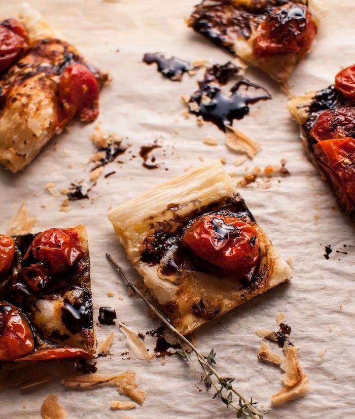 tarte aux tomates cerise rouges avec une réduction du vinaigre de balsamique et des herbes fraiches