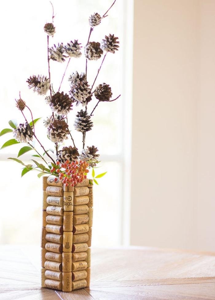 que faire avec des bochons de liège, vase de bouchons de liege avec des brindilles d arbre et de pommes de pin a l interieur