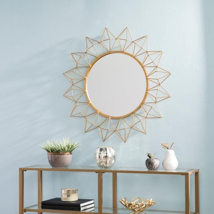 modèle de miroir doré en forme soleil, décoration salon aux murs bleu pastel avec meubles et objets à finition or