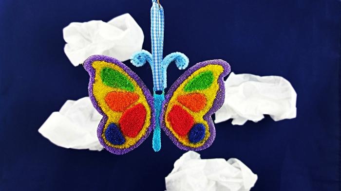 activité manuelle maternelle sur le thème de noël, ornement de noël papillon décoré avec du sable, bricoler avec du sable