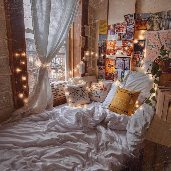 deco chambre de reve avec un lit cosy surchargé de coussins, deco murale de photos et pages de livre, guirlande lumineuse interieur