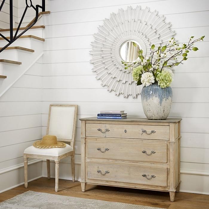 comment décorer l'espace sous escalier, design entrée rétro chic aux murs bois blanc avec meubles bois clair et miroir en forme soleil