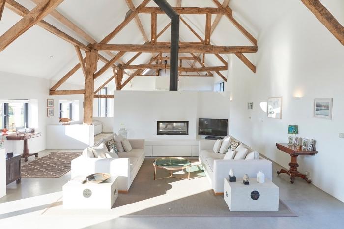 design intérieur minimaliste en blanc et bois, idée aménagement grange en salon loft avec poutres bois apparentes