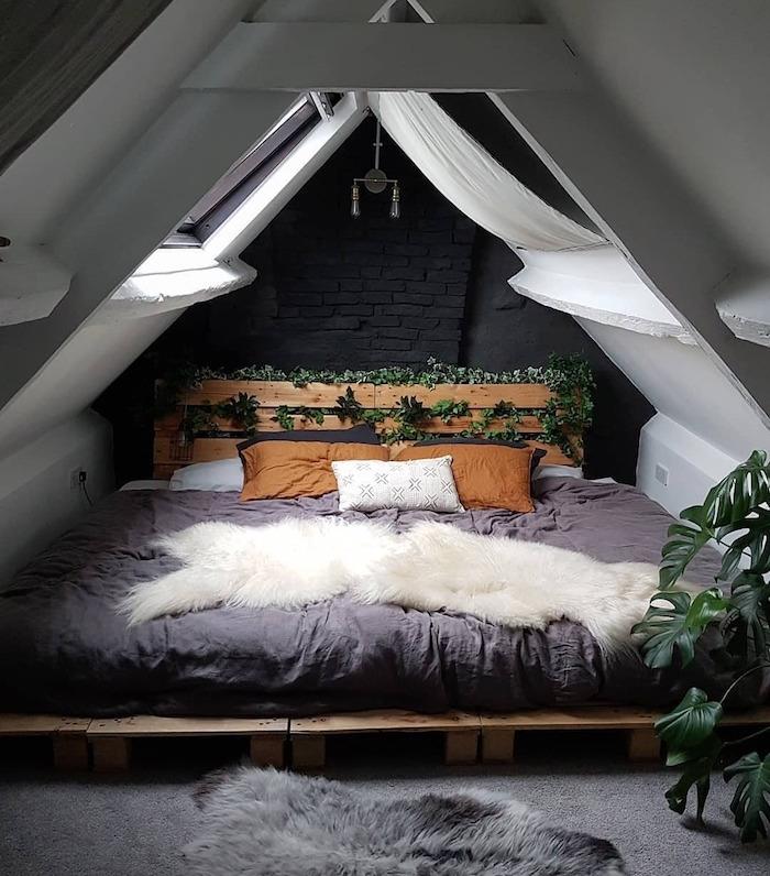 deco chambre sous comble, tete de lit végétalisée et liet en palette de bois a faire soi meme, tapis gris moelleux et peau de mouton grise, ossature bois apparente, linge de lit gris, marron, blanc