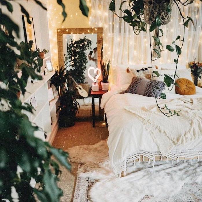 tendace deco jungle avec des plantes vetes d interieur, chambre blanche deco avec coussins gris, jaune moutarde et blanc, guirlande lumienuse sur rideau blanc