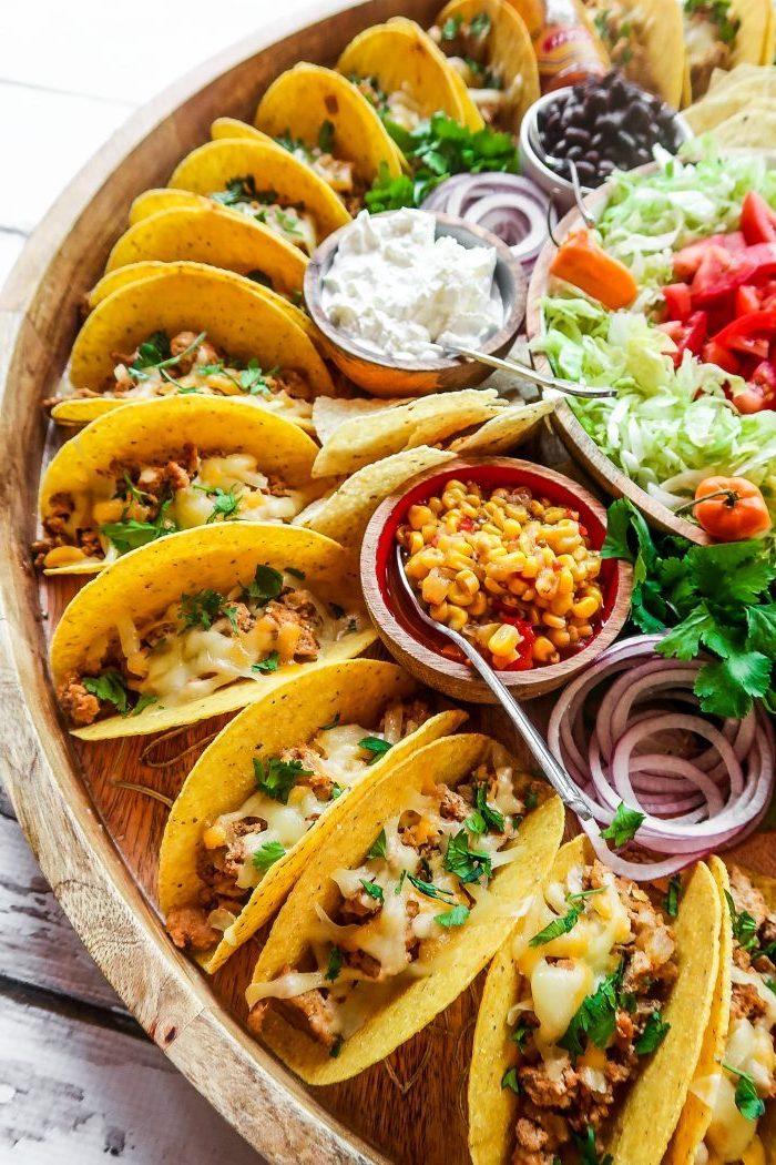 mini-tacos apéritifs au poulet, fromage frais et persil haché, plateau avec bouchées de tacos, sauces et salades diverses