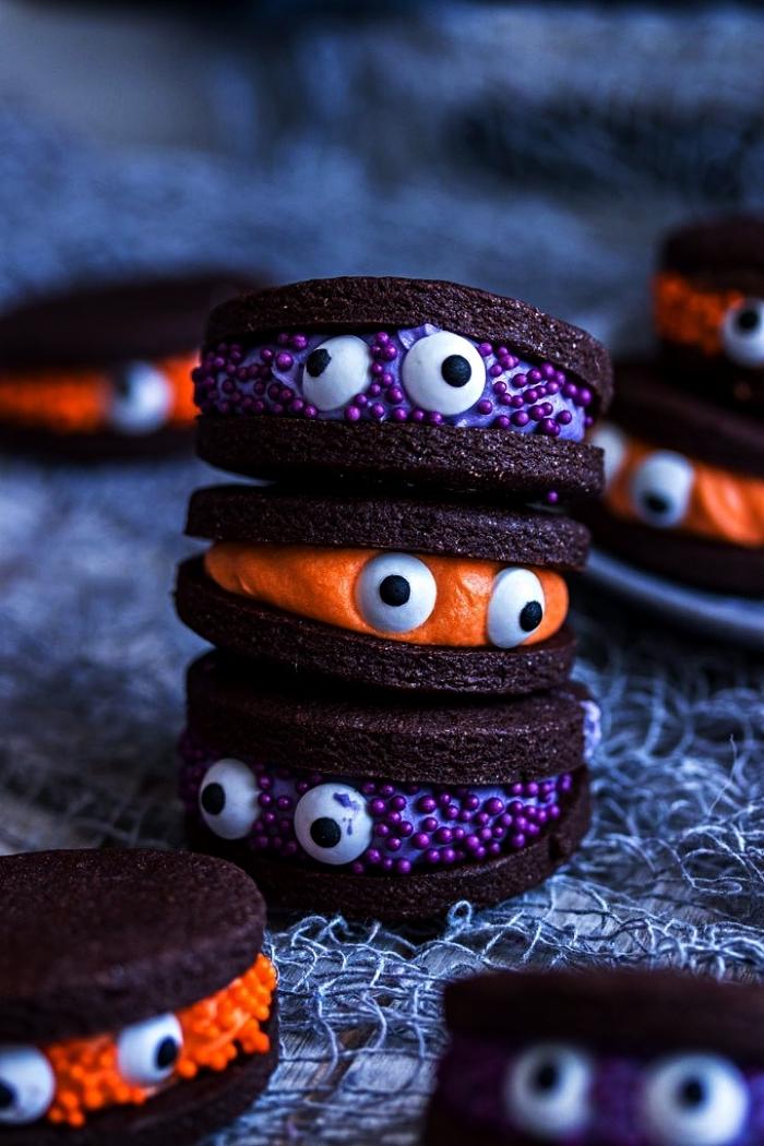 biscuits sandwichs petits monstres d'halloween au chocolat et glaçage coloré orange ou violet, recette halloween de friandises effrayantes