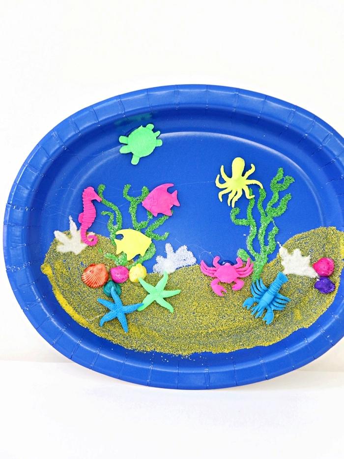 activité manuelle maternelle sur le thème de l'été, fabriquer un aquarium en assiette plastique décorée de sable