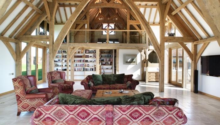 comble aménageable de style rustique au plafond et murs en bois, déco salon blanc et bois avec meubles tissu rouge et vert