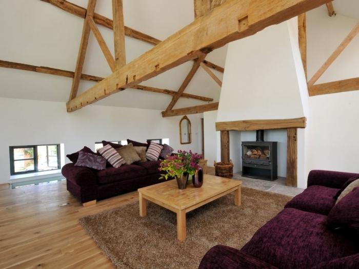 idée transformation grange en habitation, décoration salon rustique avec cheminée, meubles canapés tissu violet foncé