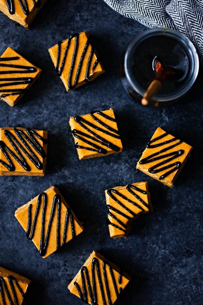 recette vegan de cheesecake à la citrouille au glaçage noir de sésame noir, barres de tarte à la citrouille aux couleurs de halloween, idée de dessert pour un repas halloween