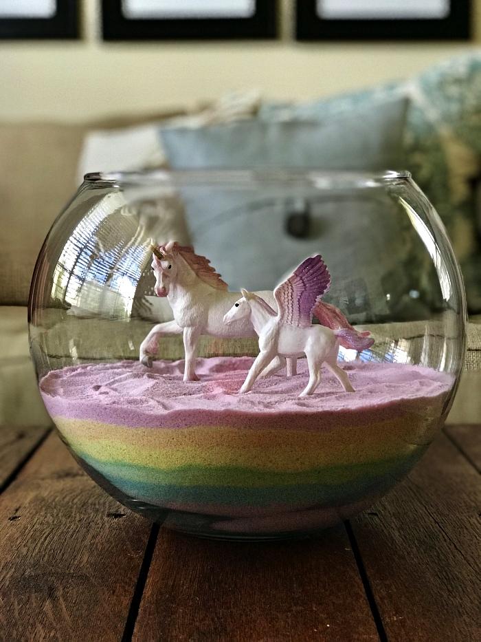 centre de table façon terrarium rempli de couches de sables aux couleurs de l'arc-en ciel et décoré de figurines licornes