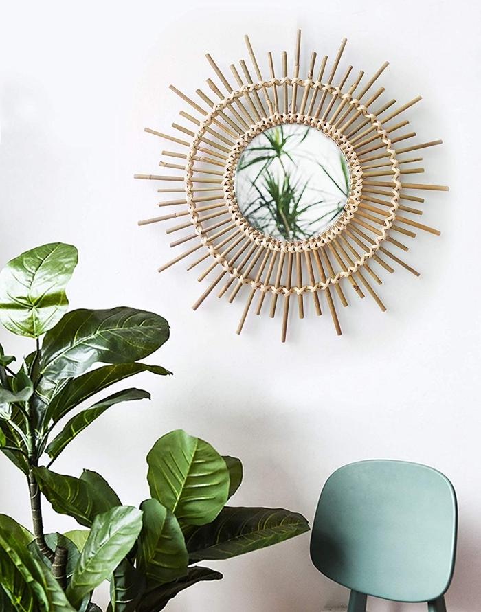 modèle de miroir rotin dans une pièce aux murs blancs avec meubles chaise vert pastel et plantes d'intérieur