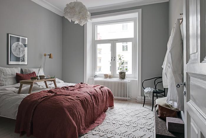 décoration chambre à coucher scandinave en gris et blanc, couverture de lit rouge, tapis tricot, suspension blanche, parquet bois clair