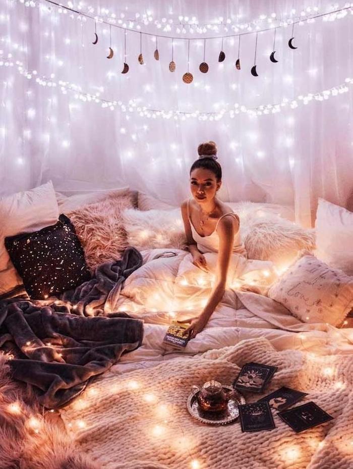 deco chambre de reve avec lit super cosy avec entassement de coussins moelleux et toute sorte de plaids et couvertures chaudes, guirlande lumineuse pour decorer baldaquin