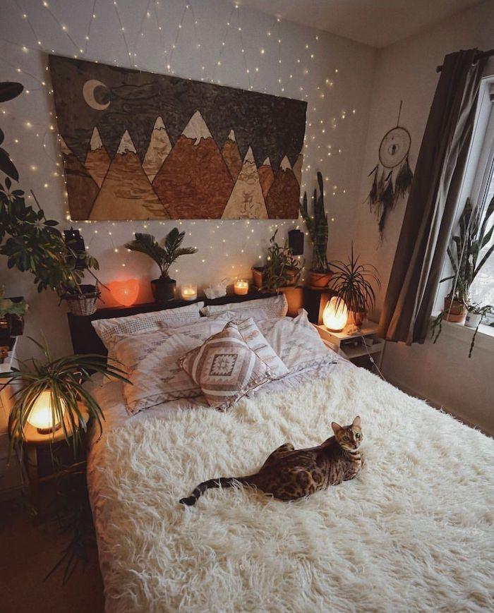 chat mignon sur un lit recouvert d une peau de mouton blanche, deco tete de lit végétale, paysage montagne dessin sur panneau, attrape reve deco murale