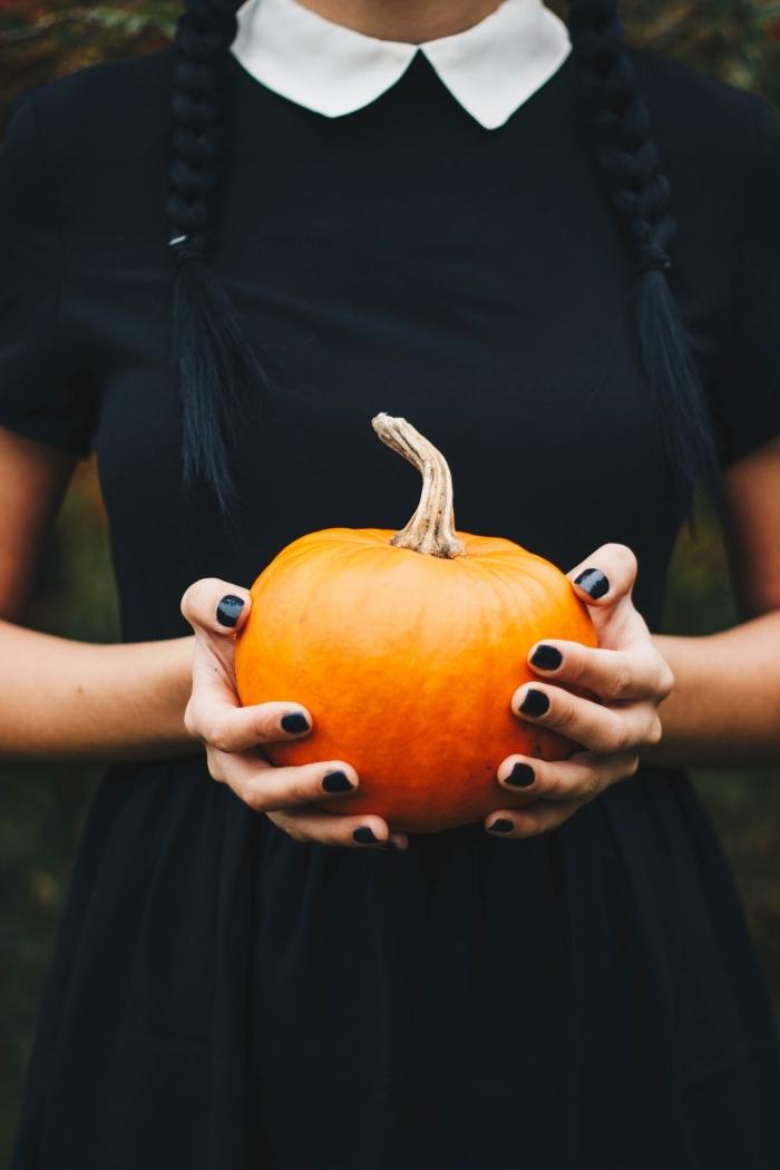 photo halloween de jeune fille déguisée en sorcière habillée en robe noire avec ongles noirs et citrouille symbole Halloween