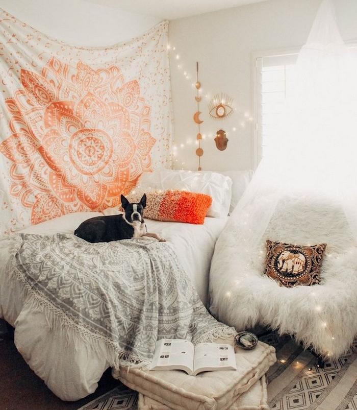chien mignon sur un lit à d;eco orientale, deco murale tissu, guirlande lumineuse, canapé recouvert d une peau de mouton blanche, lit décoré de linge de lit blanc, couverture gris et blanc mandala