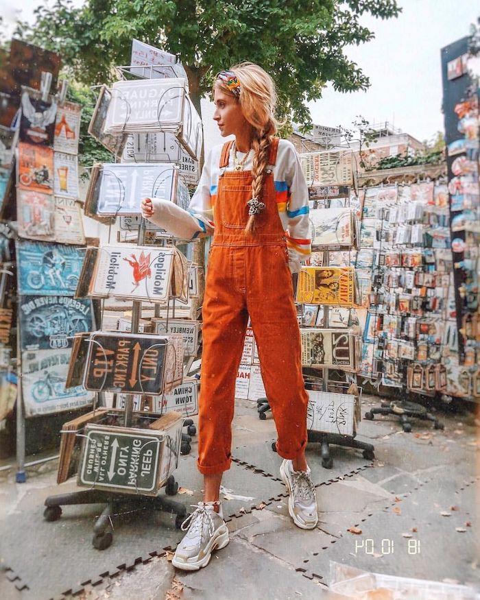 Salopette jean orange, fille bien habillée, blouson blanc avec lignes colorés, baskets géantes, habillé pantalon à pince, tenue casual qui va bien avec la coiffure tresse