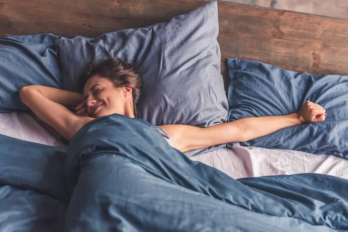 Femme dans son lit qui se réveille heureuse, idée comment prendre bon soin de soi