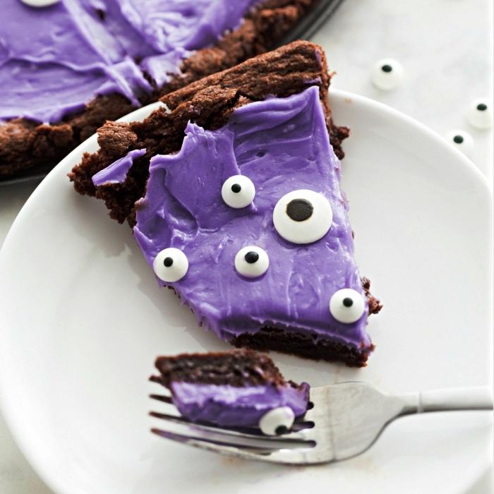 dessert rapide pour le repas halloween, recette de cookie géant façon monstre d'halloween au chocolat et son glaçage coloré violet