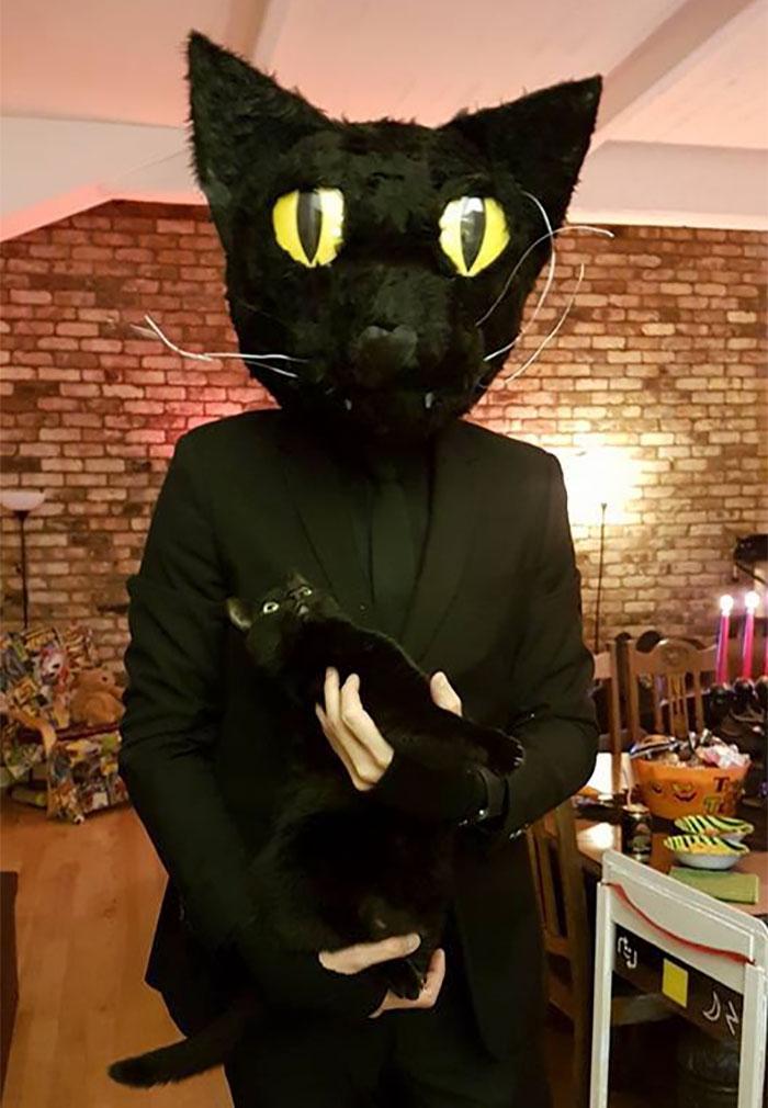 Se déguiser comme son chat noir, le chat sur la photo avec l'homme en son costume noire avec masque de chat noir