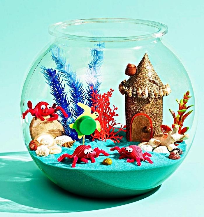 activité manuelle été sur le thème de la mer, aquarium marin avec un fond de sable bleu et des figurines d'animaux marins