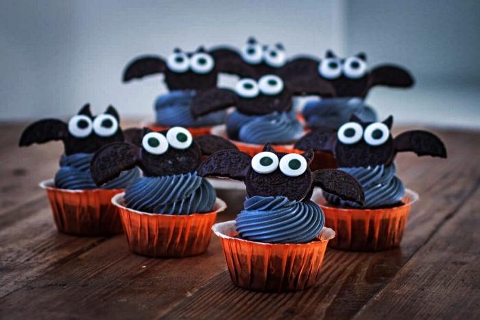 cupcakes d'halloween au glaçage noir décorés de chauves-souris en biscuits oreo, dessert simple et rapide pour le repas halloween