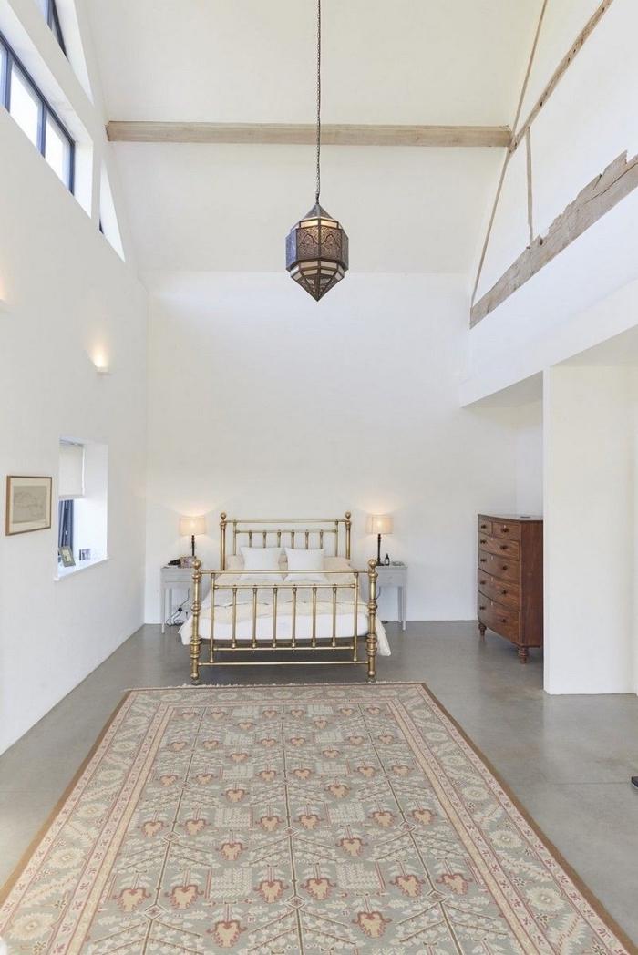 deisgn chambre blanche au sol ciment avec lit à cadre doré et meuble bois foncé, aménagement grange en chambre