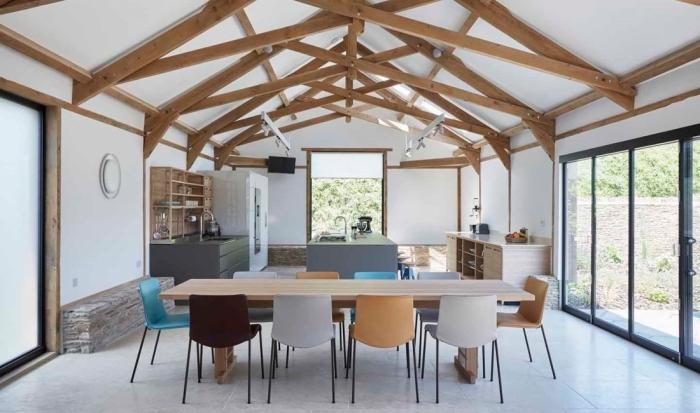 transformation grange en habitation, design cuisine parallèle avec îlot central ouverte vers la salle à manger au sol effet ciment
