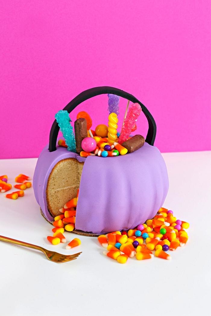 gateau d'halloween en forme de citrouille au glaçage en pâte à sucre violet, décoré de confiseries d'halloween