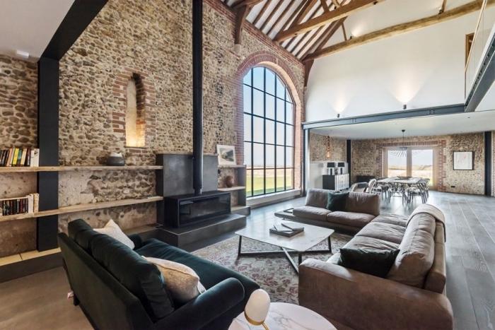 idée transformation grange en habitation, design industriel dans un salon loft au sol à effet ciment avec meubles foncés