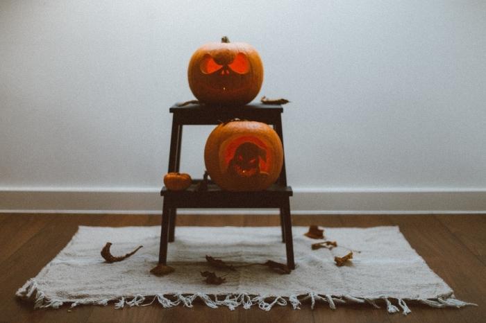 diy décor pour halloween avec citrouilles jack'o, idée citrouille halloween sculptée posée sur table bois basse