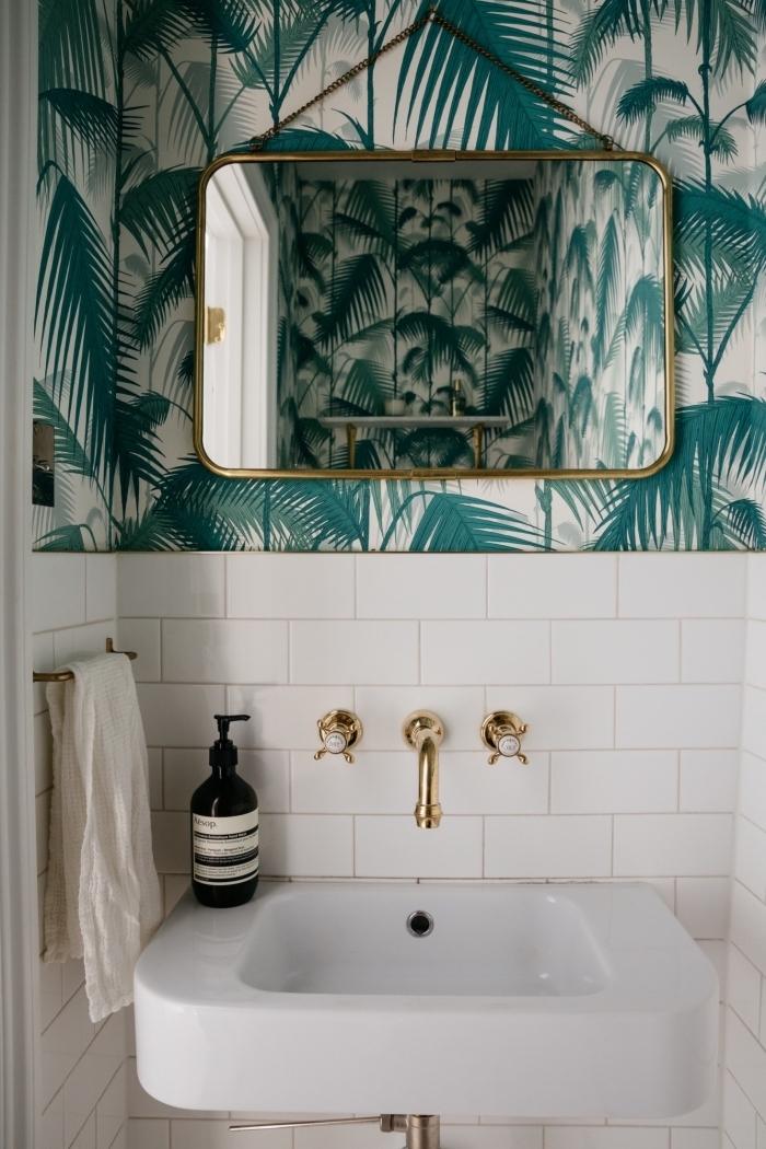 ambiance tropicale dans les toilettes, décoration pièce en blanc avec accents dorés et papier peint effet feuilles tropicales