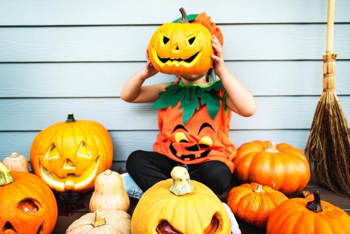 idée costume enfant en citrouille halloween, photo halloween avec citrouilles sculptées et petit enfant déguisé