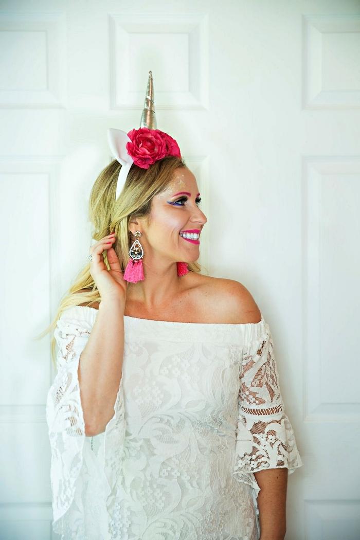 maquillage halloween simple à inspiration licorne avec trait-t'eye-liner bleu, déguisement de licorne glamour avec robe blanche en dentelle, un serre-tête licorne et des boucles d'oreilles pompons rose