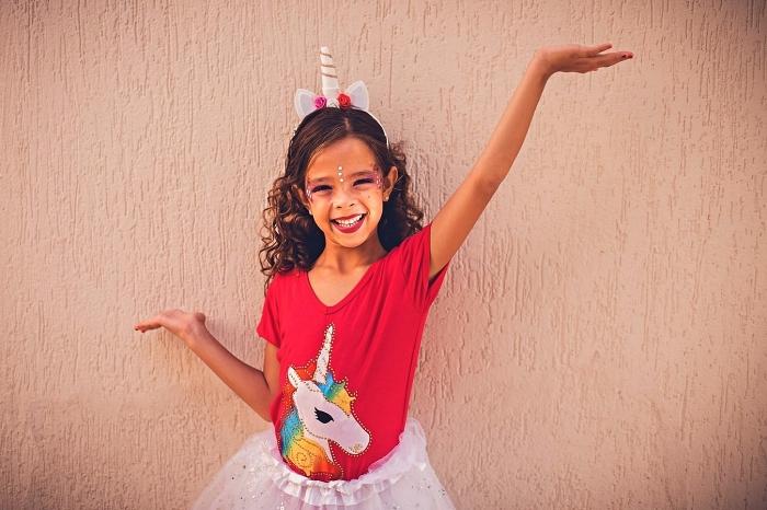 déguisement licorne fille avec t-shirt imprimé licorne, jupe tutu et un serre-tête corne de licorne, maquillage de licorne facile avec paillettes et strass