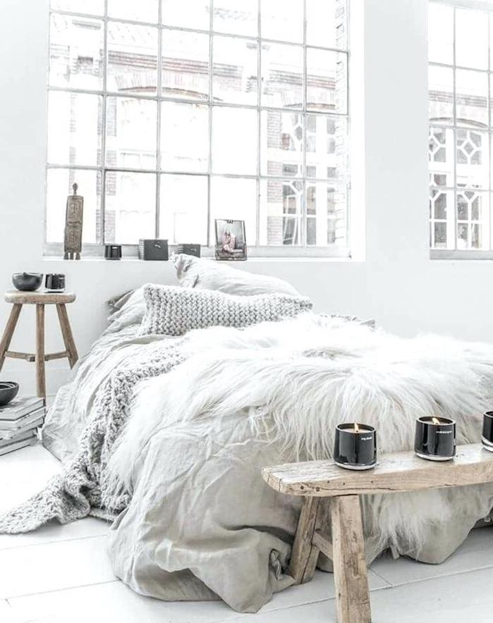 couverture de lit à mailles grise, bout de lit bois brut dans une chambre nordique style scandinave, table de nuit tabouret et bougeoirs aromatiques, deco loft romantique