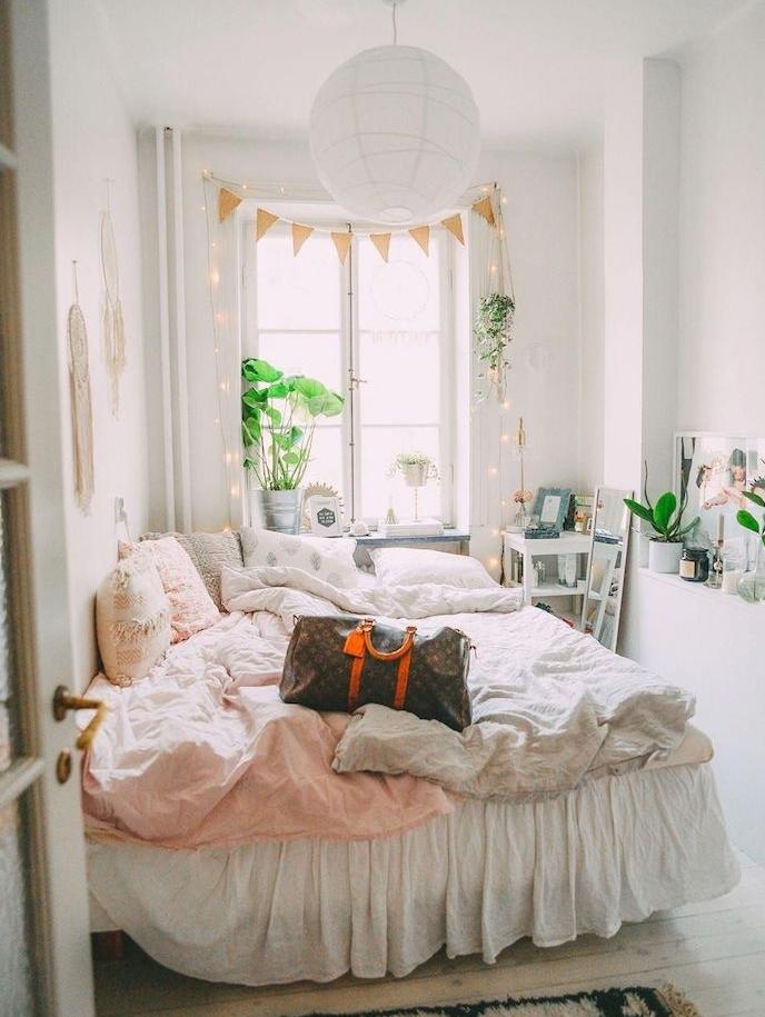 suspension blanche boule, linge d elit rose et blanc, guirlande lumineuse deco cadre de fenetre, parquet bois clair, plantes vertes d interieur pour une deco scandinave