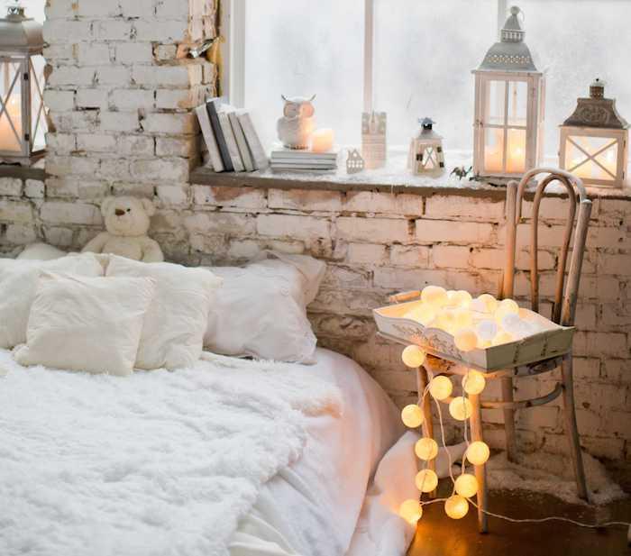 deco loft industriel romantique d hiver, chaise bois brut avec guirlande boule, linge de lit blanc avec peau de mouton blanche, deco rebord de fenetre en lanternes, livres et figurines decoratives