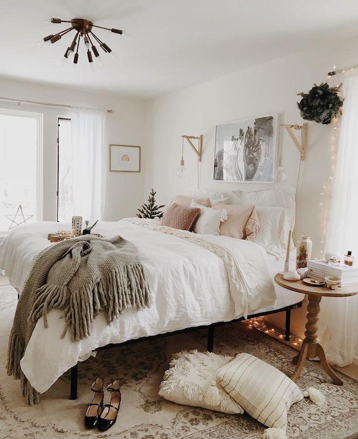 couverture grise moelleuse sur un lit en ligne rose et blanc, coussins blanc et rose, murs blancs, guirlande lumineuse decorative, tapis cocooning, deco chambre romantique feminine