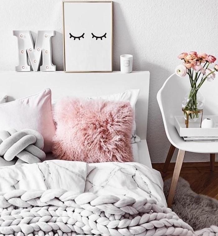 coussin cosy rose et coussin noeud gris, plaid à grosses mailles gris clair, murs blancs, tete de lit deco cadre, bougie lettre lumières LED, table de nuit chaise scandinave blanche